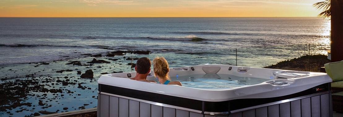 Illustratie: foto van man en vrouw in Caldera Spa Tahitian whirlpool. Samen kijken ze uit over de oceaan.
