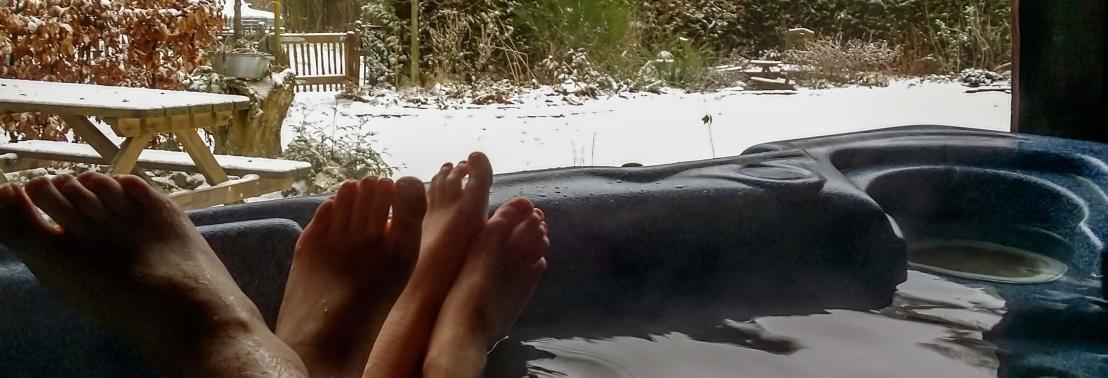 Illustratie: foto van stelletje dat vanuit de spa kijkt over een besneeuwde tuin. Jacuzzi en sneeuw, een geweldige combi.